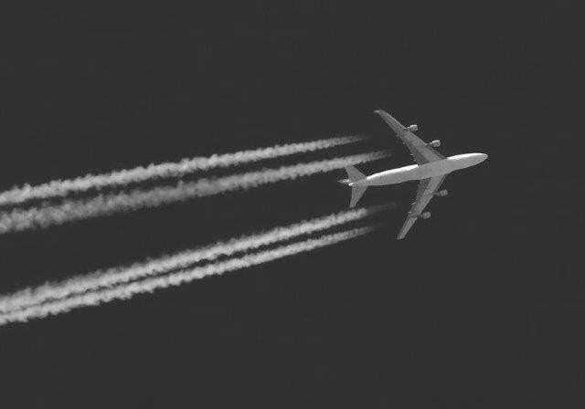 Black and white image of an airplane flying overhead with trails behind each wing